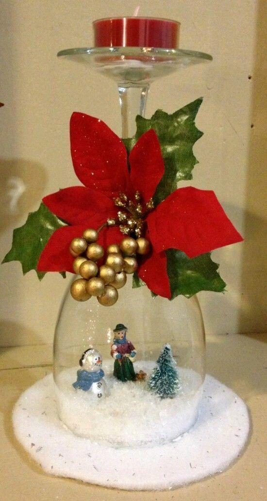 Crea una escena navideña en el interior de una copa de cristal