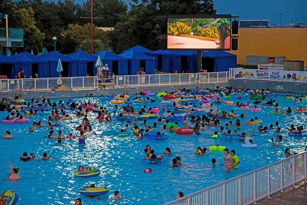 People Floating In The Wave Pool At Hurricane Harbor While Watching A Movie During Dive In Movies In Arlington Dive In Movie Movies Under The Stars Wave Pool