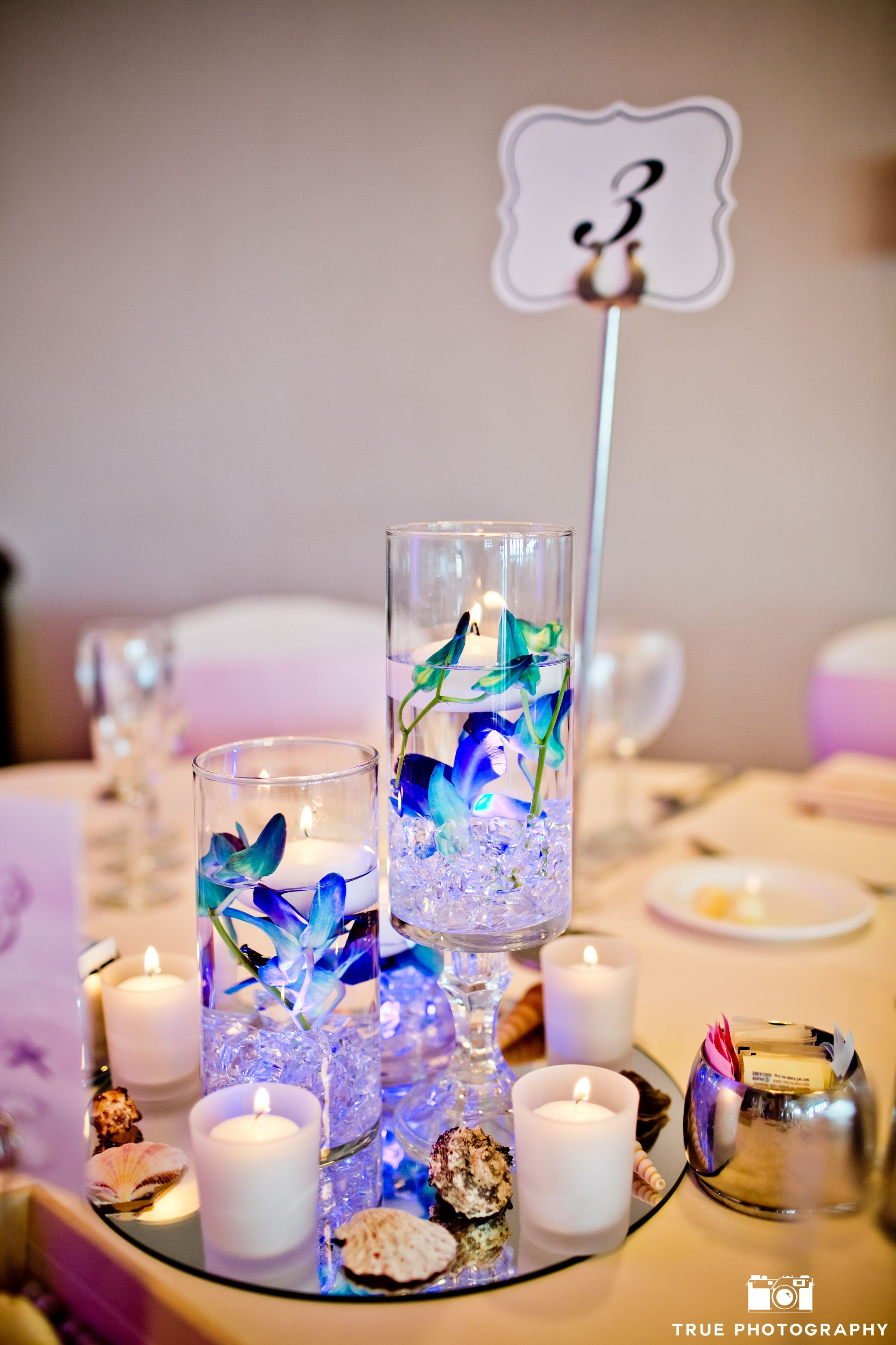 Floating candles in various size glass vases with  clear rocks and blue dendrobium orchids with shells, votive candles and mirrors brought in the sea side theme of this wedding reception.  Thank you Hannah Smith Events & True Photography
