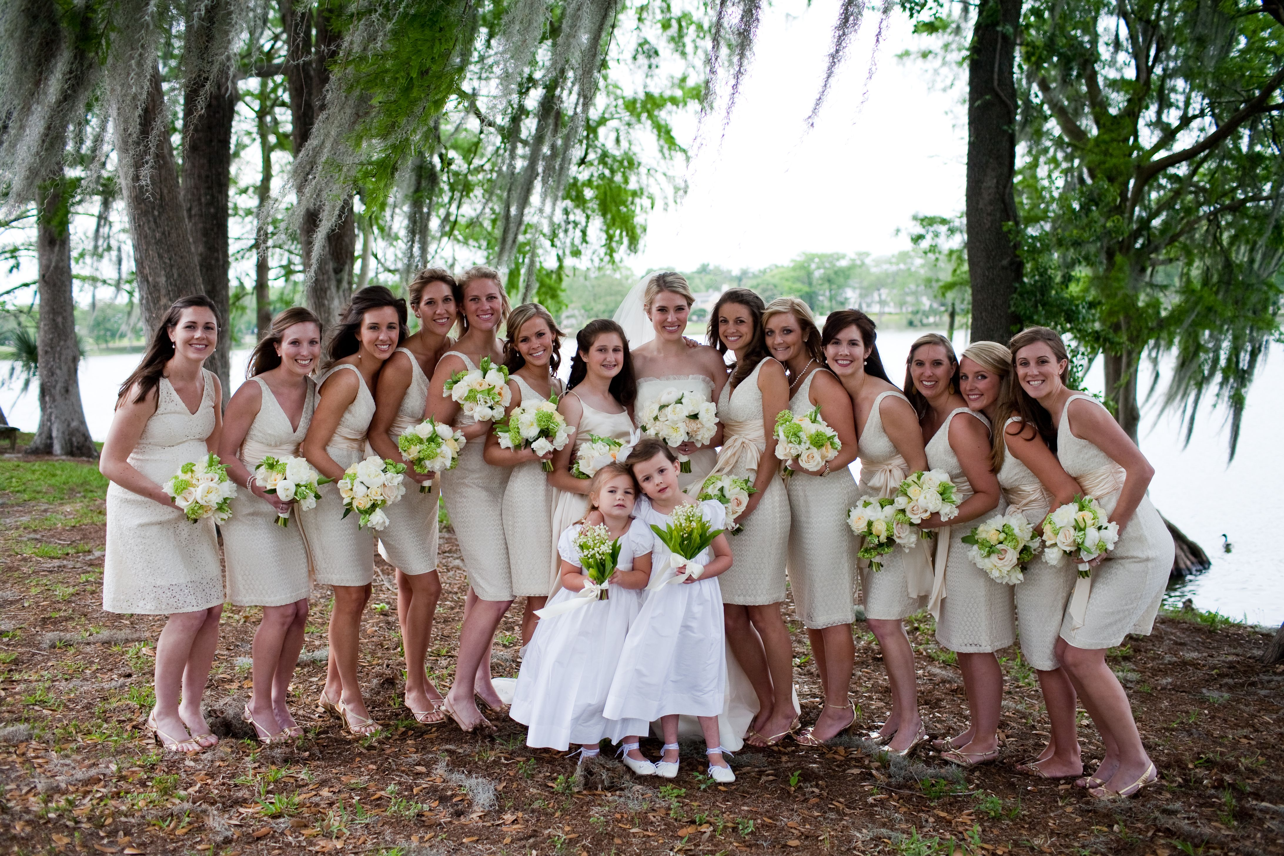 A wedding palette of spring greens, ivory and white. Bridesmaids in ivory lace dresses carry bouquets of peonies, garden roses and tulips, and flower girls hold bouquets of lily of the valley.
