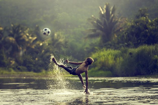 Thai young boy play soccer and over head  Premium Photo