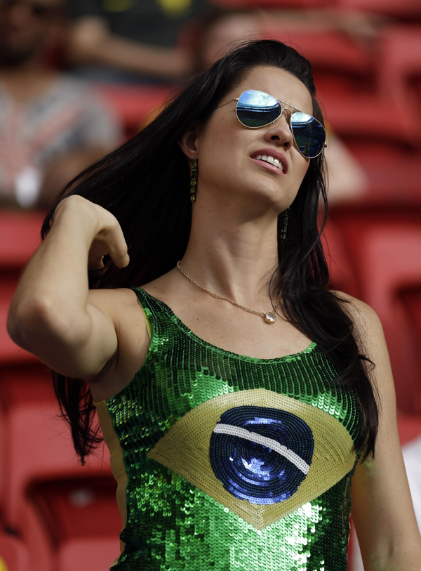 A Brazil supporter adjusts her hair before the World Cup third-place soccer match between Brazil and the Netherlands at the Estadio Nacional in Brasilia, Brazil, Saturday, July 12, 2014 | Brasil 2014: Las chicas más bellas del Mundial de Fútbol - Yahoo Deportes