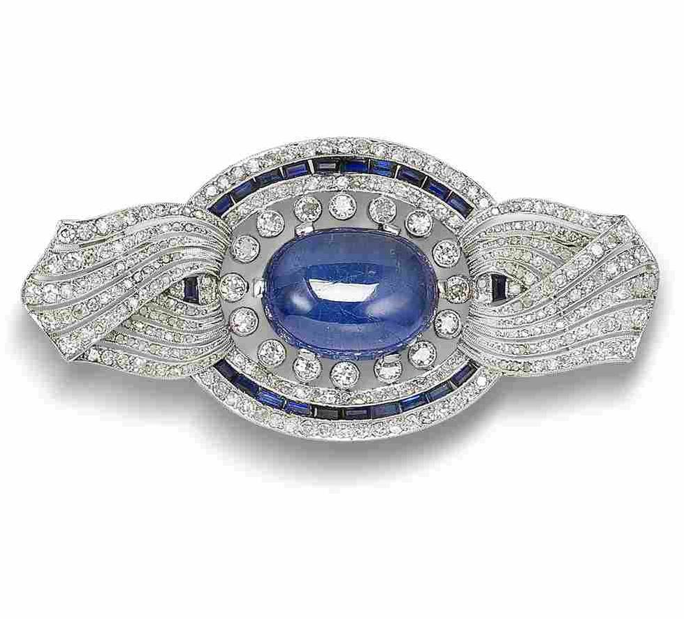A sapphire, synthetic sapphire and diamond brooch, circa 1915  The oval cabochon sapphire within a pierced oval surround with twisted ribbon finials, millegrain-set throughout with single and rose-cut diamonds and accented with a row of calibré-cut synthetic sapphires, single-cut diamonds approximately 4.00 carats total, width 7.0cm