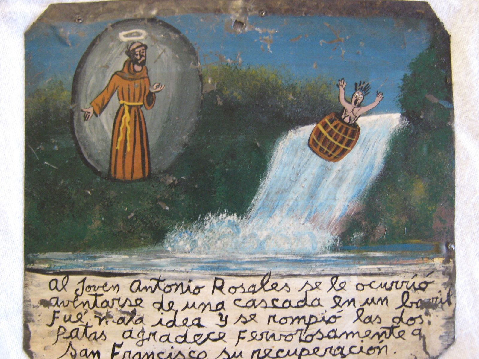 The writing in Spanish says: Antonio Rosales decided it was a good idea to jump off a waterfall inside a barrel. It was a bad mistake, because he broke both his legs. He gives thanks to San Francisco for his recovery.