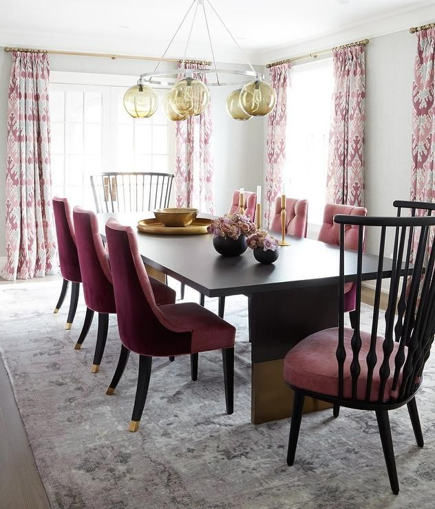 Gray dining room features an amber glass ring pendant hangs over a ...