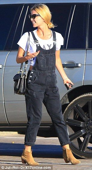 Bang on trend: Annabelle, 32, courted attention in a white statement T-shirt and black denim dungarees as she walked alongside her boyfriend