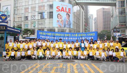 """7月13日下午,韩国法轮大法佛学会在中共驻韩大使馆前举行记者会,声援中国民众控告江泽民。有的中国游客激动地现场签名声援诉江大潮。截至当天,韩国已有至少116名法轮功学员向中共最高检察院、最高法院和国务院总理李克强邮寄了""""刑事控告状"""",要求""""尽快逮捕江泽民""""。 - 国际新闻"""