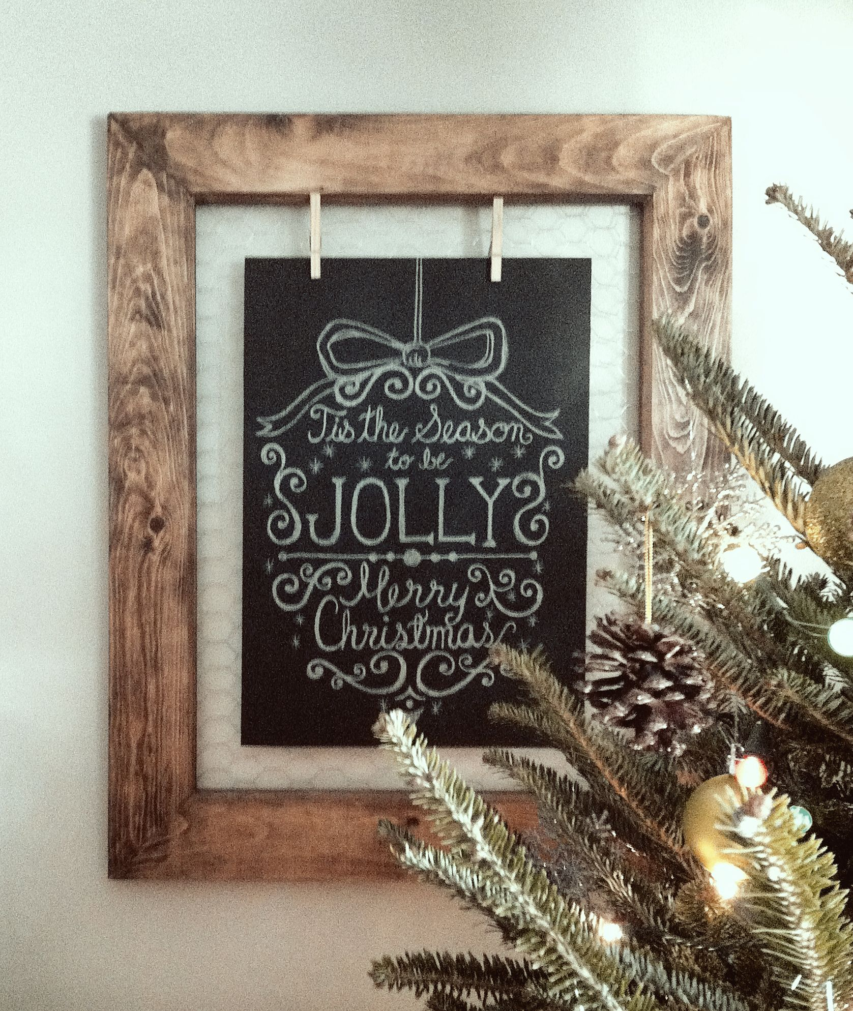custom wood frame with chicken wire backing and a typography chalkboard suspended with close pins