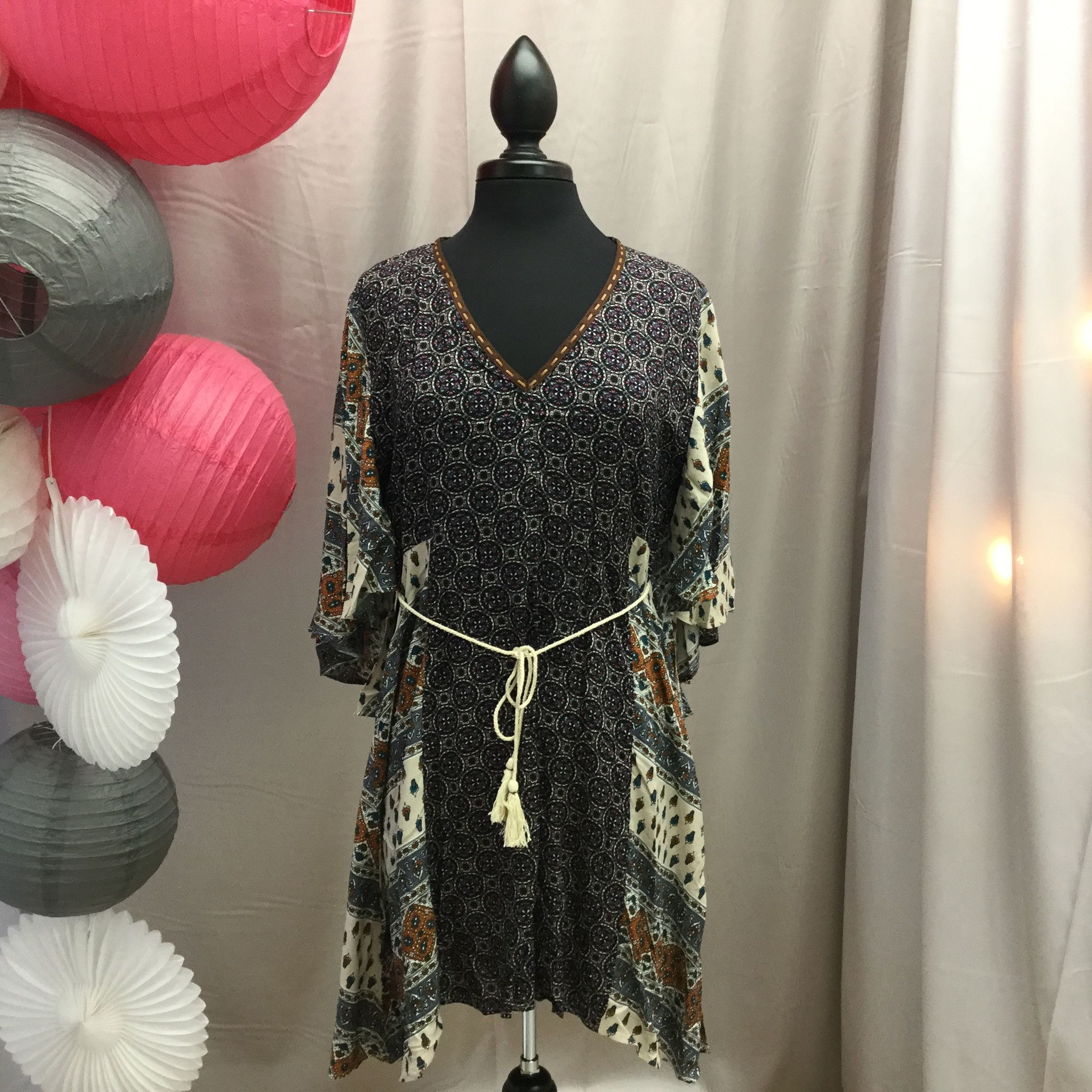 TRENDSETTING, GORGEOUS!! We cannot say enough about how adorable this dress is...especially when paired with our mocha vest!! Details everywhere... mixed prints, woven laced neckline,tassel rope tie,