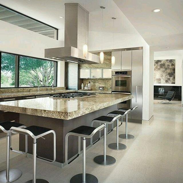 Cocina en isla con uso de tonos tierra en contraste con tonos ...
