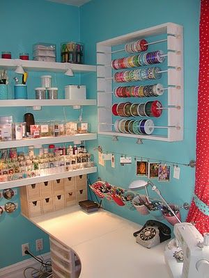 Photos of different craft rooms. No text ... I liked this one: the ribbon rack; the pen cups, the wooden boxes, sewing machine, lighted shelves. Looks organized, functional and homey.