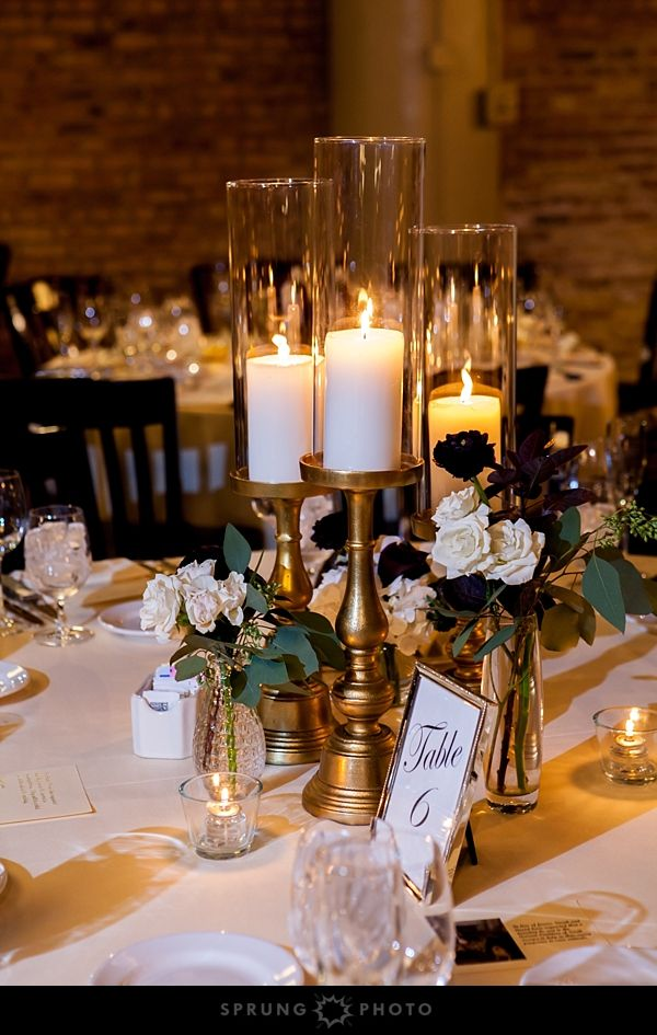 Tall Candles In Gold Candleholders And White And Maroon Flowers Gold Wedding Centerpieces Tall Wedding Centerpieces Cheap Wedding Table Centerpieces