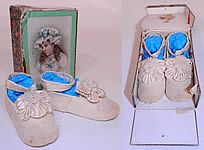 "Mary jane baby shoes and box, 1900. They are made of ivory velvet with silk rosette floral petal trim on the instep front vamps. They have an ankle strap button closure, leather bottom soles and rounded square toes. The shoes measure 4.5"" long and 1.5"" wide. They come in a pretty paper box covered with floral rose wallpaper along the sides and a beautiful litho print girl on the front, with an open top and side."