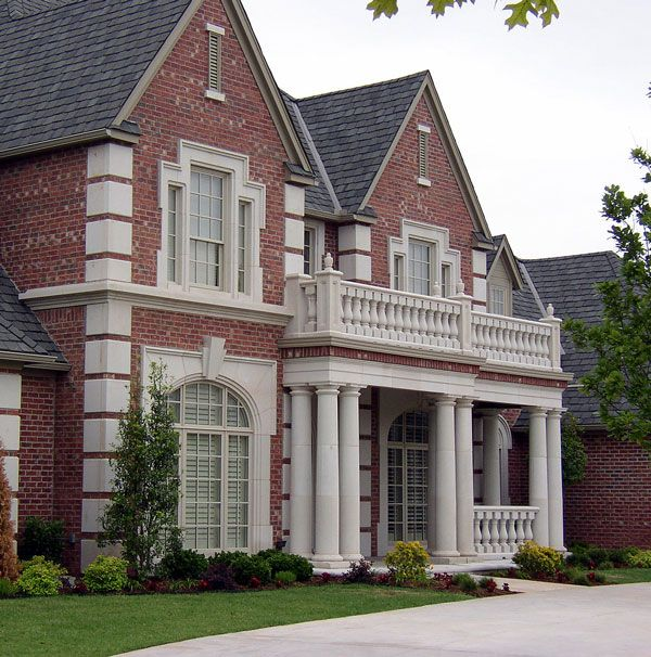 residential home with cast stone entry, tuscan columns, quoins