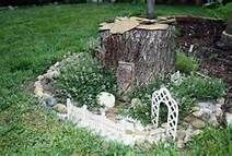 stump fairy house surrounded by thyme