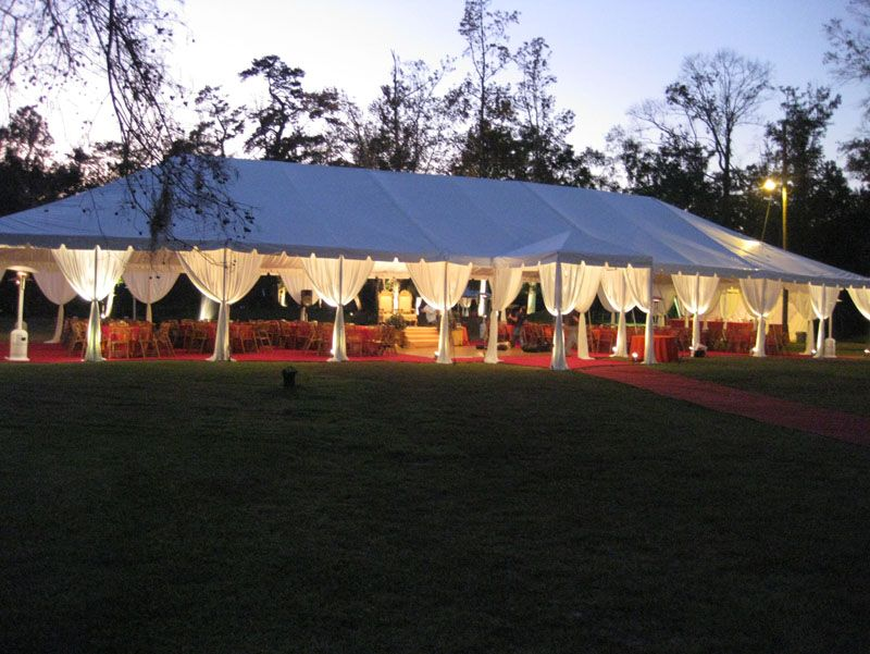 white tent with leg drape bamboo folding chairs and red carpet