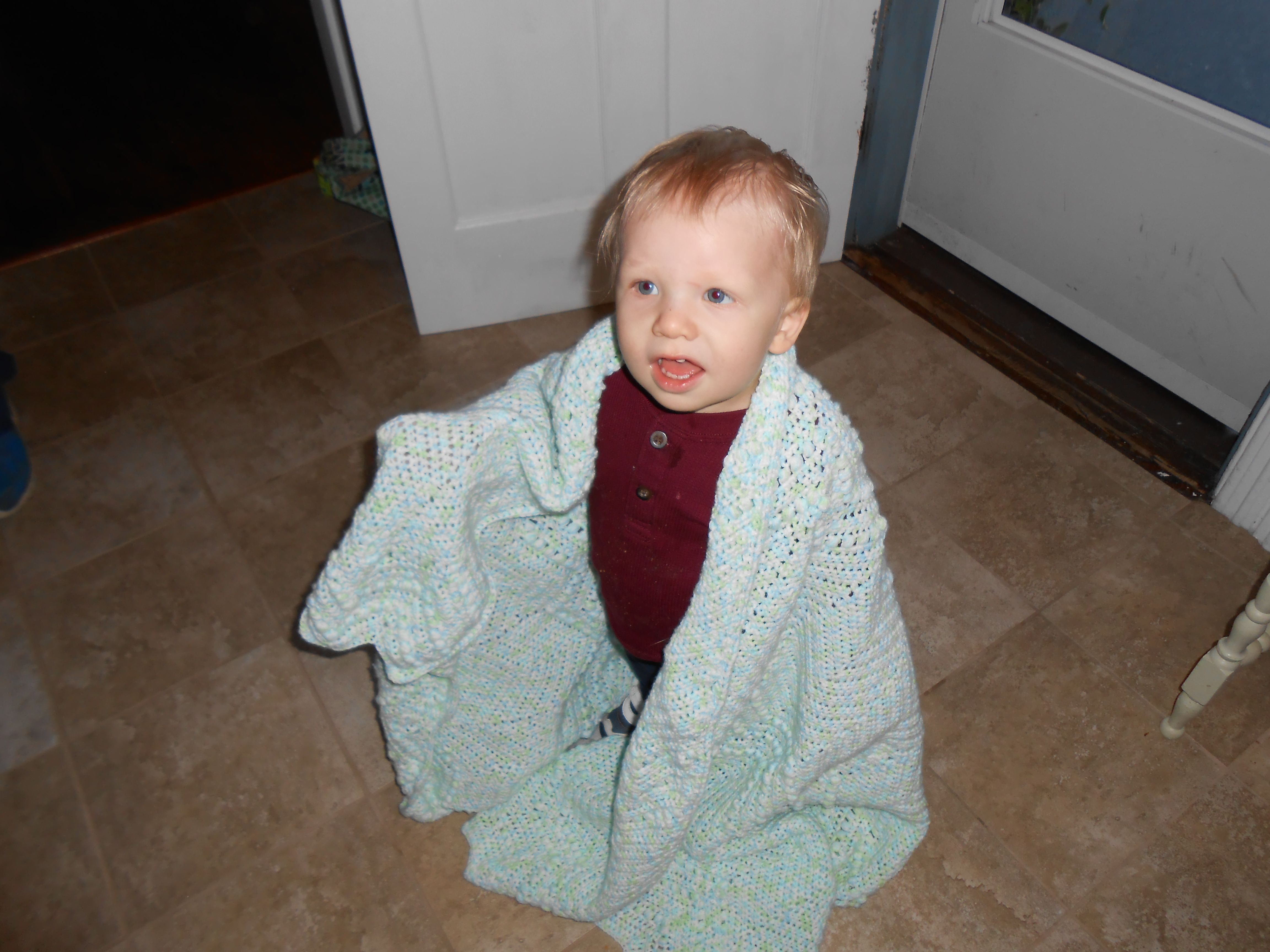 my grandson with the blanket I crocheted for him!