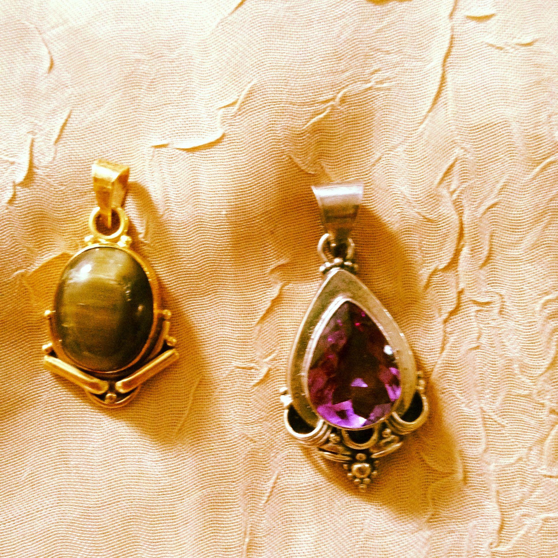 Pingentes:1-com gema de turmalina olho de gato em prata com banho de ouro e, 2-com gema de ametista em prata.