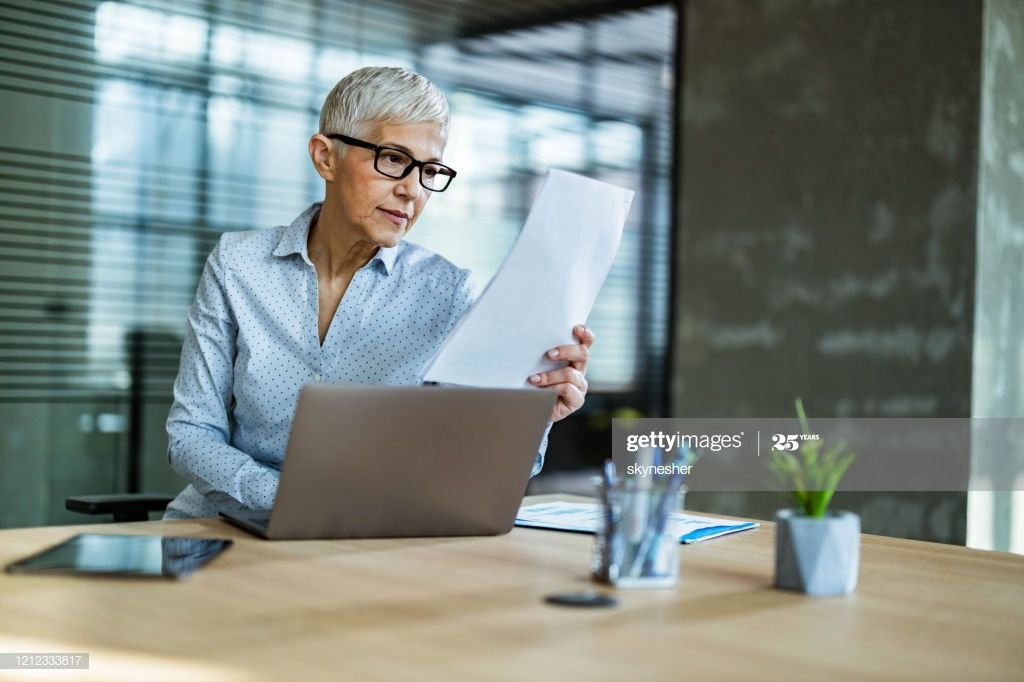 Senior Businesswoman Reading Reports While Working On Laptop In The Office Photo #Ad, , #AFF, #Reading, #Reports, #Senior, #Businesswoman