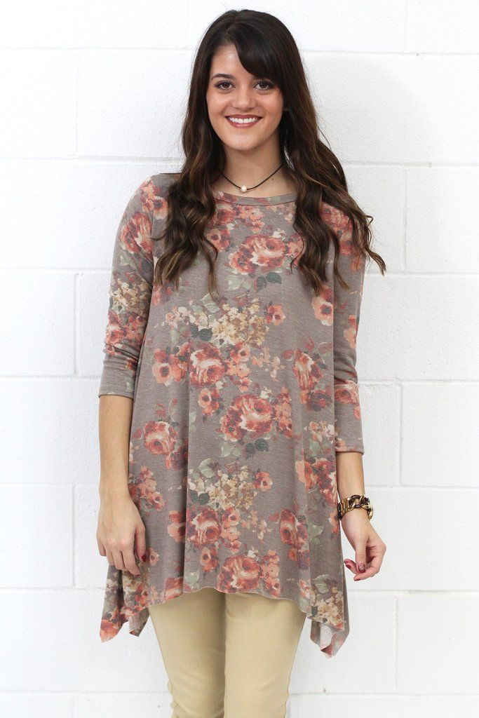 Super cute and soft washed out floral tunic top with shark bite / handkerchief sides. Three quarter length sleeves. Dark taupe in color with burgundy, rose, cream, and green mixed in. Round neck. Loose fit.