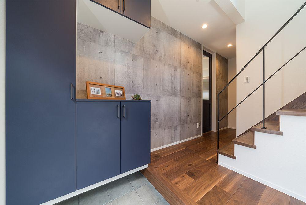 1階廊下の壁にはサンゲツ様のスタイリッシュなコンクリート打ちっぱなし風のクロス フルハイドアとの組み合わせで 空間を広くすっきりと見せてくれますね アイアンの手すりやネイビーブルーの建具と相性バッチリ 無垢の風合いを生かしたフローリングとも合ってます