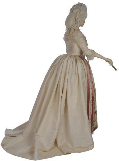 """Robe à l'anglaise: ca. 1780-1785, French (probaby), silk, embroidered cotton with silks, silk ribbon, lined with glazed linen, boned. """"This gown demonstrates the fashionable styles in women's formal dress of the 1780s. The hoop has changed from the square shape of earlier decades to a round profile. A stomacher is no longer needed, because the gown now meets in the front. The cream silk is adorned only at the edges with an embroidered band, ribbon and a stencilled fringe..."""""""
