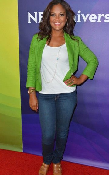 Laila's flirty and feminine in a green blazer, white top, jeans, and gold sandals