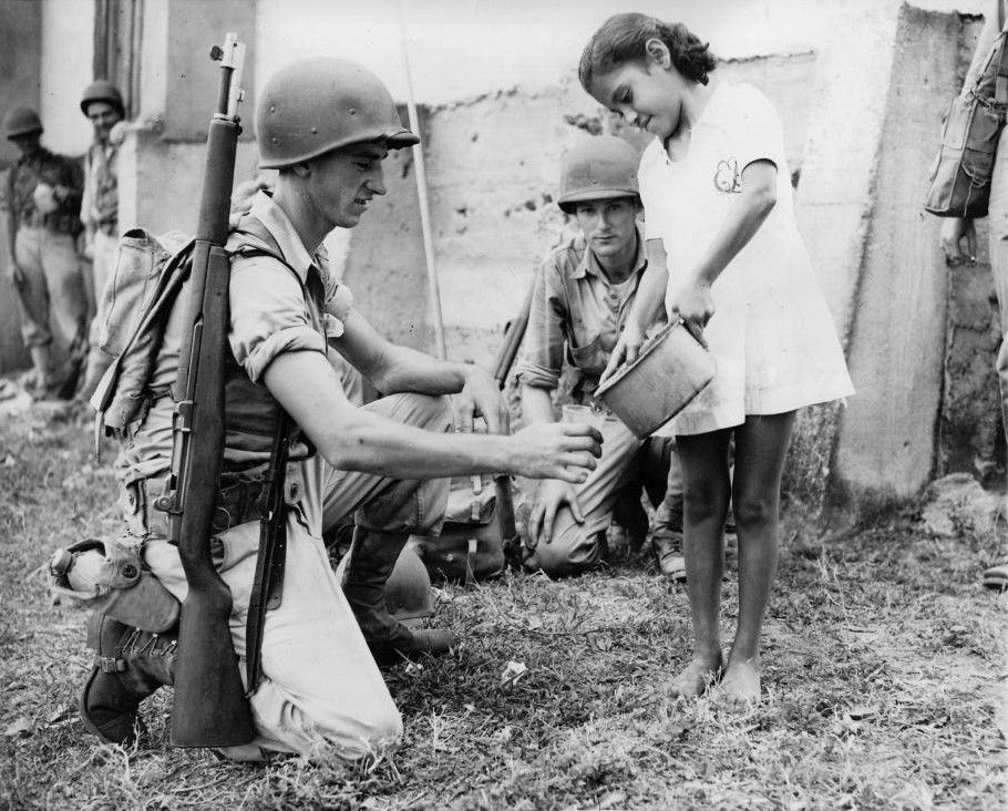 US soldier getting water from a girl during a training exercise, Panama Canal Zone, 1942. Although Panama was too far away for any direct attack against, it remained closely guarded for fear of sabotage. Also, German U-boats often lingered around its approaches in the hope of easy pickings. Note the GI's M1 Garand rifle.
