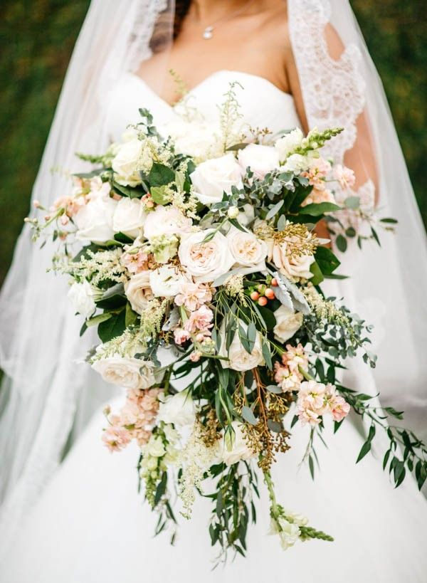 Romantic overgrown wedding bouquet in blush, peach, and ivory | Image by Nate + Lori