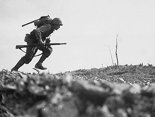 On Okinawa, just 350 miles from Japan, a Marine dashes through Japanese machine gun fire while crossing a draw, called 'Death Valley' by the men fighting there. Marines sustained more than 125 casualties in eight hours crossing this valley. May 1945.