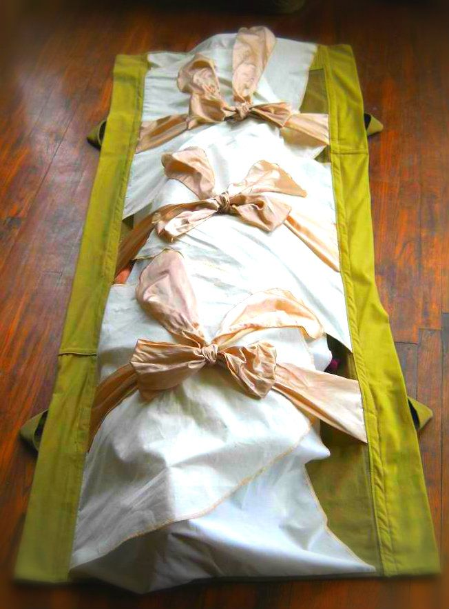 Burial Shroud With Pink Ties And A Green Background For Reference