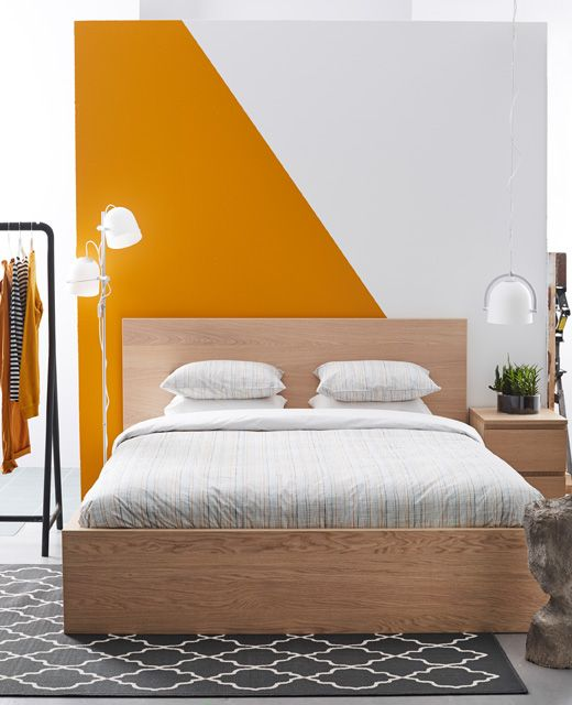 A simple, clean bedroom with a graphic orange and white wall - Orange Bedrooms