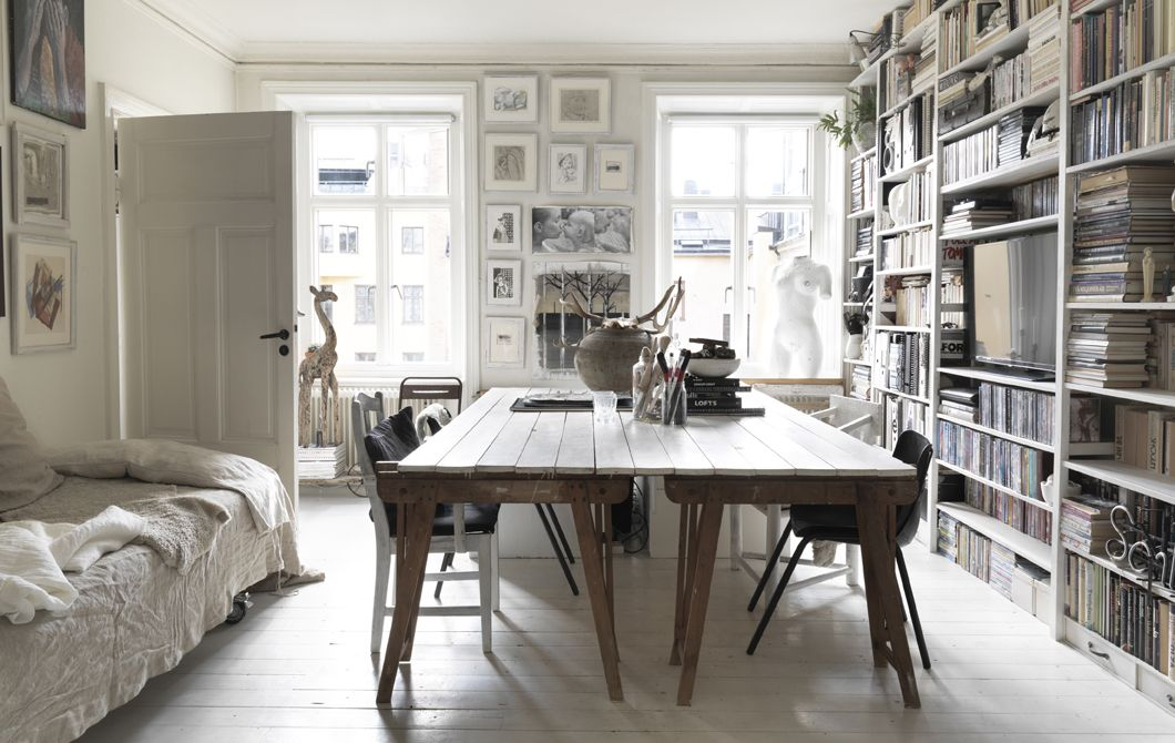 A large dining table and wall of bookshelves. be my guest
