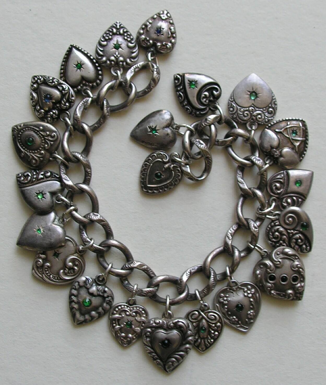Bracelet featuring antique heart charms with green (and a blue or two) pastes. Courtesy of Red Robin Antiques (Ruby Lane)