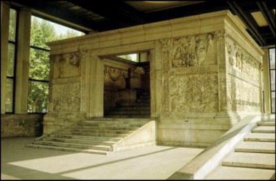 ARA PACIS DE AUGUSTO. Mármol. s.I a.c. El Senado romano acordó consagrar en el Campo de Marte un Ara de la Paz en honor de los triunfos de Augusto en Hispania y la Galia. Se alza sobre un alto pedestal escalonado, dentro de un recinto murado de 11 x 10 m., casi cuadrado, y con 2 puertas de acceso, una al E.y otra al O. El interior, decorado con relieves de guirnaldas de frutos y flores y en los exteriores Augusto encabeza una procesión junto a su familia, amigos y colaboradores.