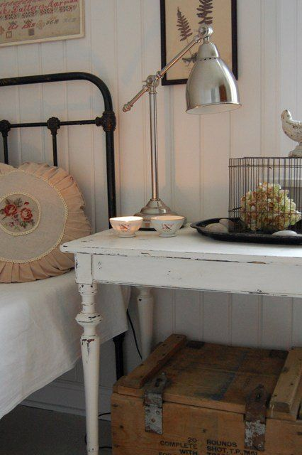 Iron bed frame, distressed side table, whitewashed plank wall.