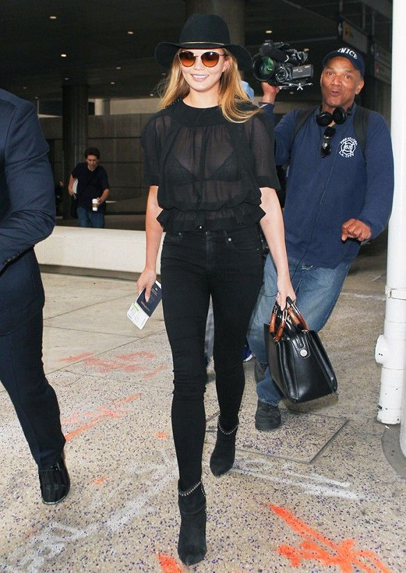 Chrissy Teigen wears a sheer black blouse, skinny jeans, studded ankle boots, a fedora, and a black satchel