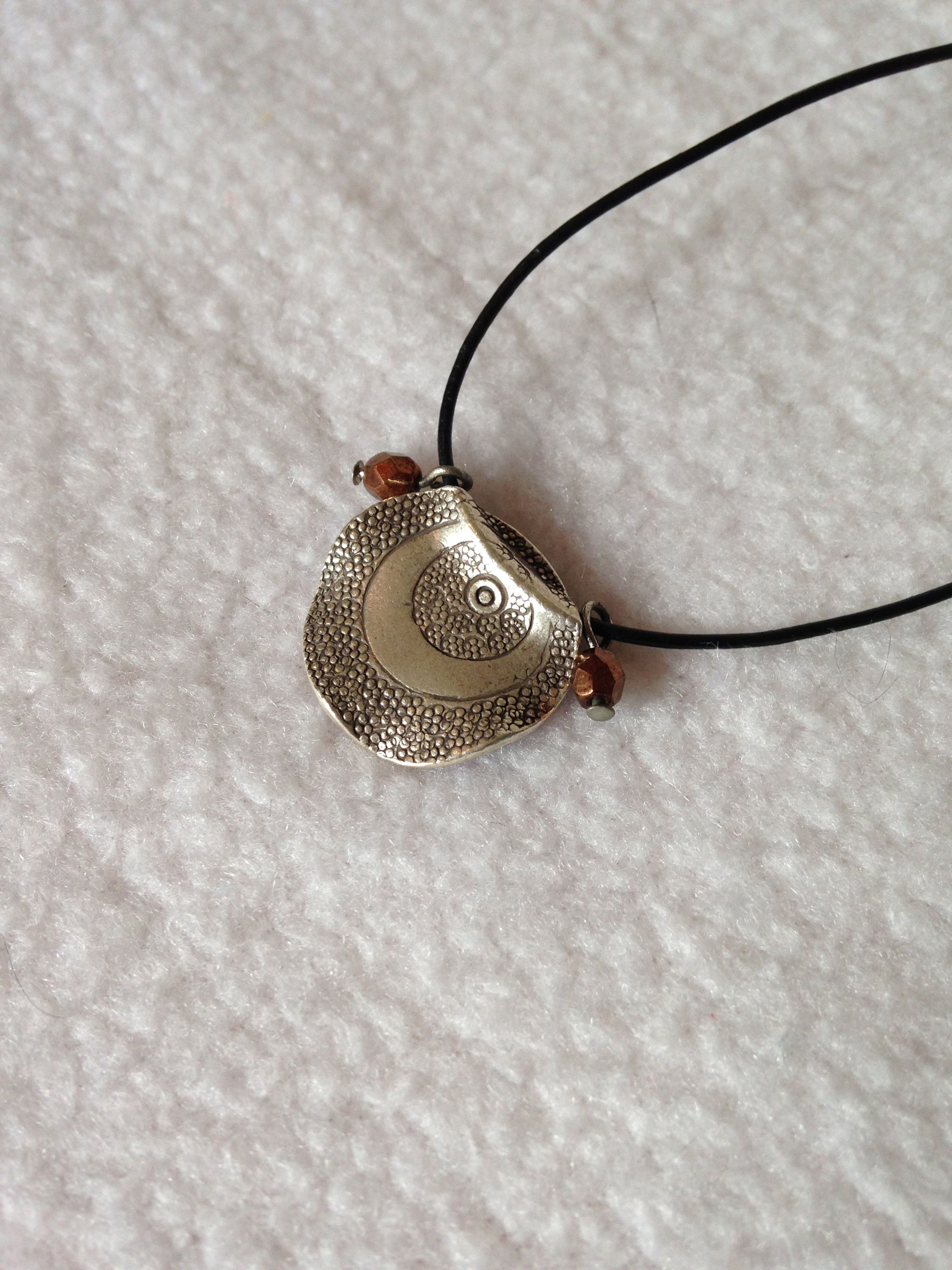 Silver hammered disc on leather cord