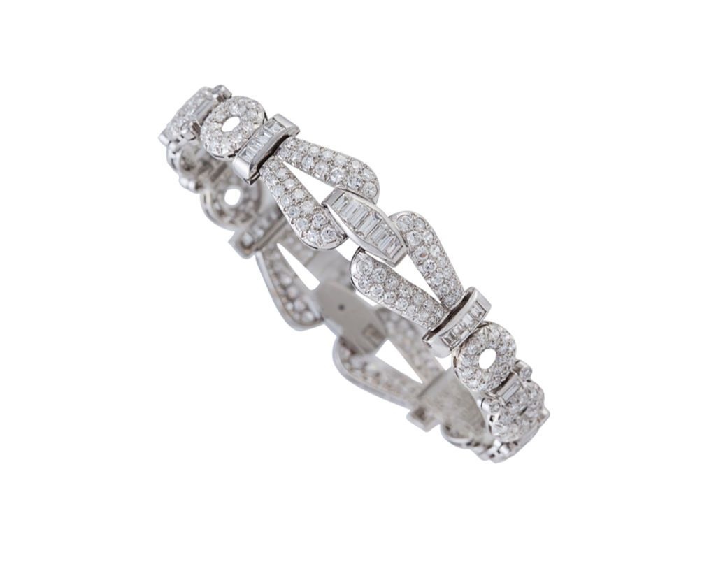 The bracelet is composed of alternating circular diamond-set links and bar links, the center and clasp are 2 buckle links.  Circa 1930.
