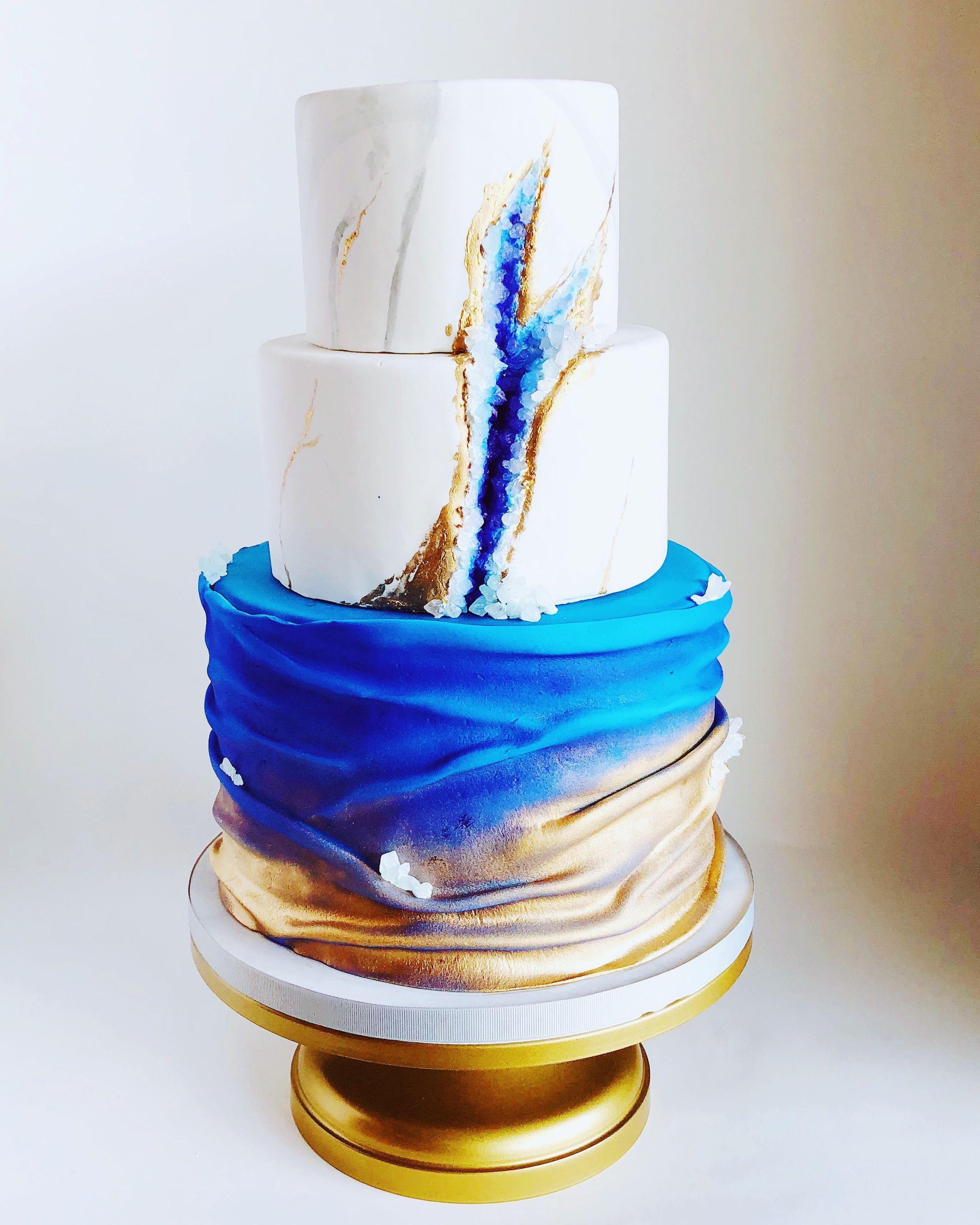 Beautiful modern blue white and gold wedding cake with
