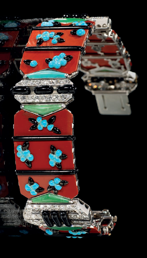 AN ART DECO MULTI-GEM, ENAMEL AND DIAMOND BRACELET, BY BOUCHERON. Of oriental inspiration, composed of four articulated jasper panels, each with applied blue and black enamel blossom clusters between black enamel line borders, joined by circular-cut diamond geometric buckle design links, with buff-top turquoise terminals, to a concealed clasp. 1925. With French assay marks for gold. Signed Boucheron. #ArtDeco #Boucheron #bracelet