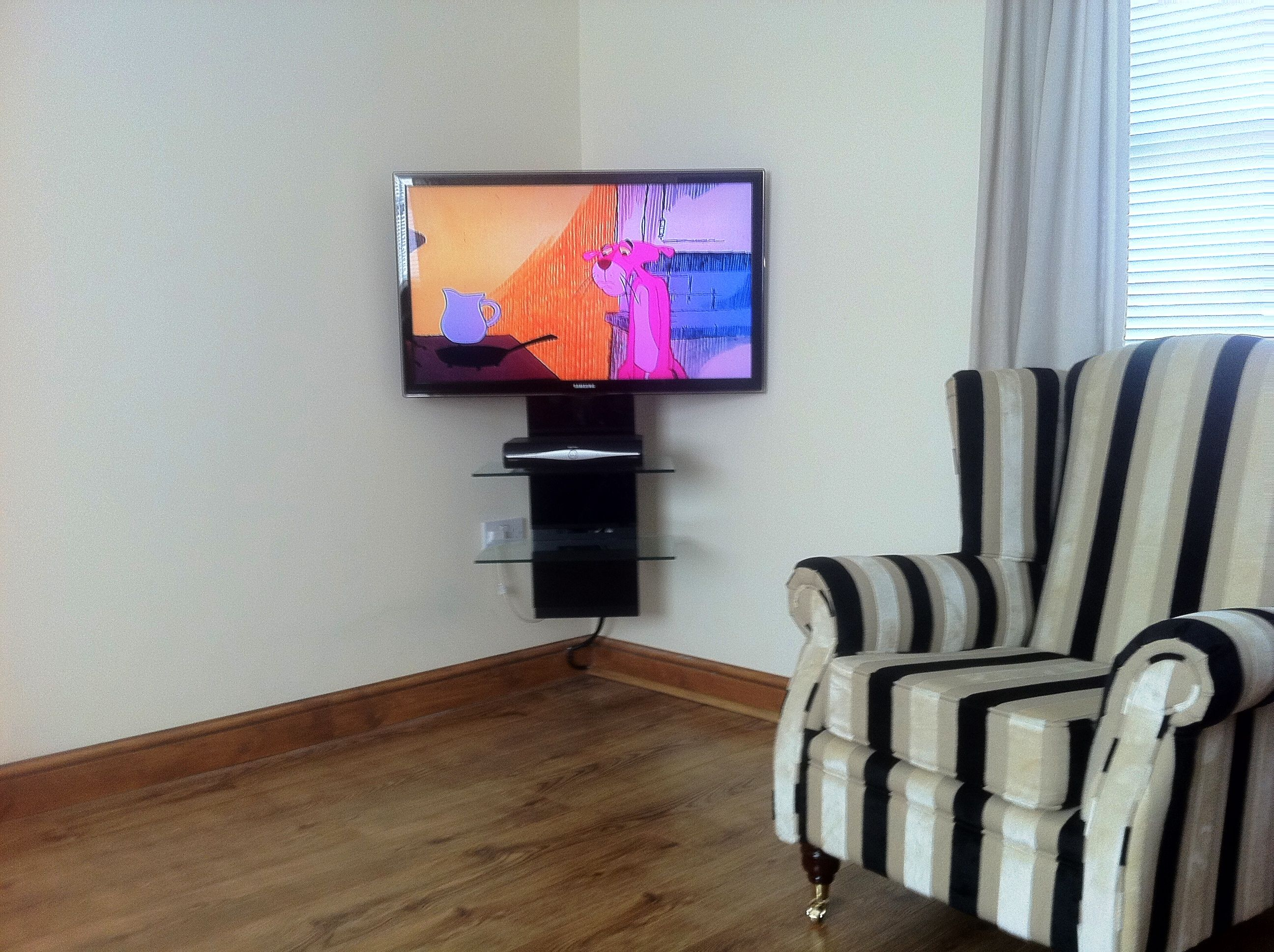 Plasma TV Wall Mounted In The Corner Of The Room On A - Corner floating wall shelf hidden bracket wall shelving corner wall