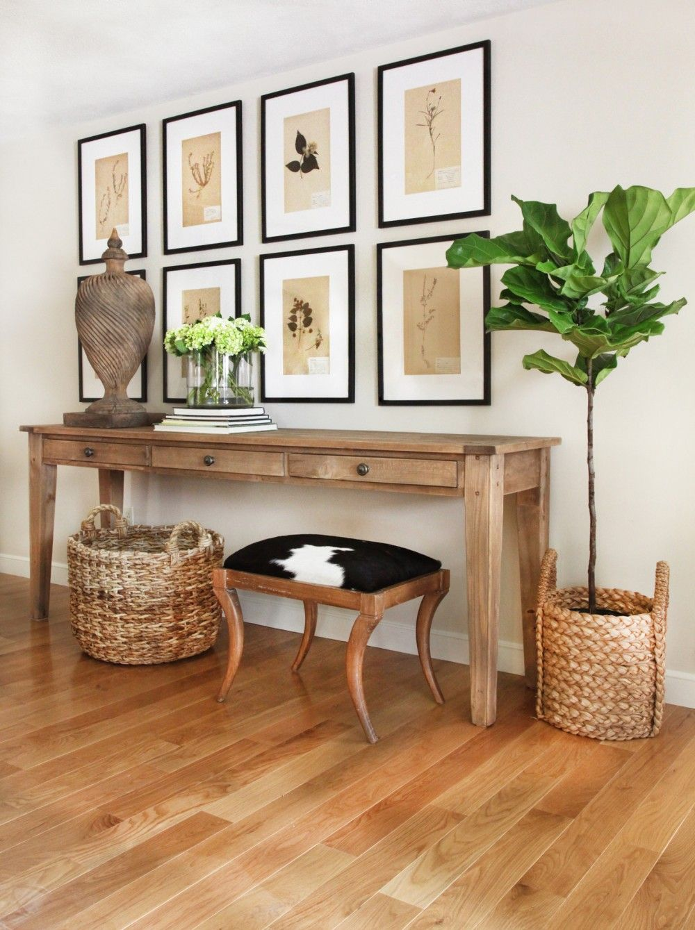 Console With Prints Arranged In Grid Basket And Cowhide Stool Farmhouse Console Table Farmhouse Family Rooms Trending Decor