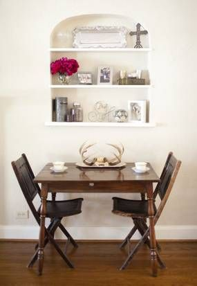 """To keep her home from """"getting too girly,"""" Sarah Harmeyer added an antique table with leather-accented folding chairs under the arched built-in shelf."""