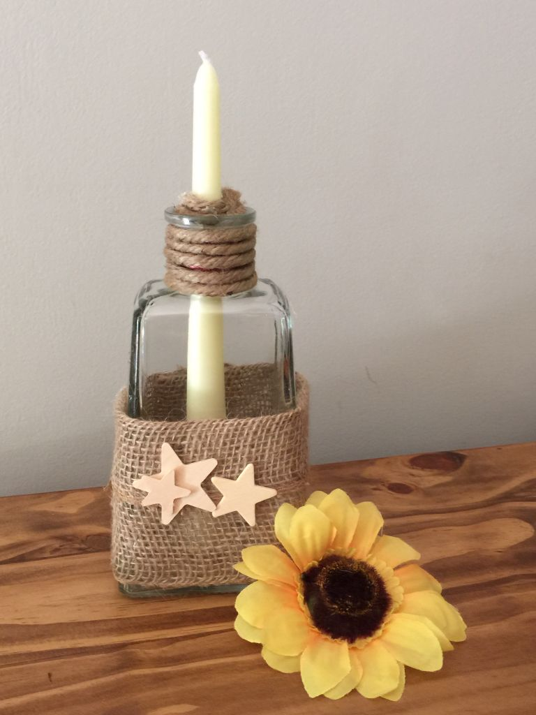 Tequila inspiration! Wrap an empty bottle with turned-down burlap and wrap the neck with twine. An additional piece of twine glued inside the neck, and left with a 'tail' allows any candle to fit safely, embellish as you like. I like stars!