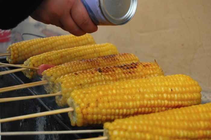Chinese Street Style Corn on a Skewer, by plateofwander.com: Skewered, brushed with oil, coated with a mix of chilli powder, cumin and salt, and roasted over coals until crunchy. What a  great idea! #Corn_on_the_Cob #plateofwander