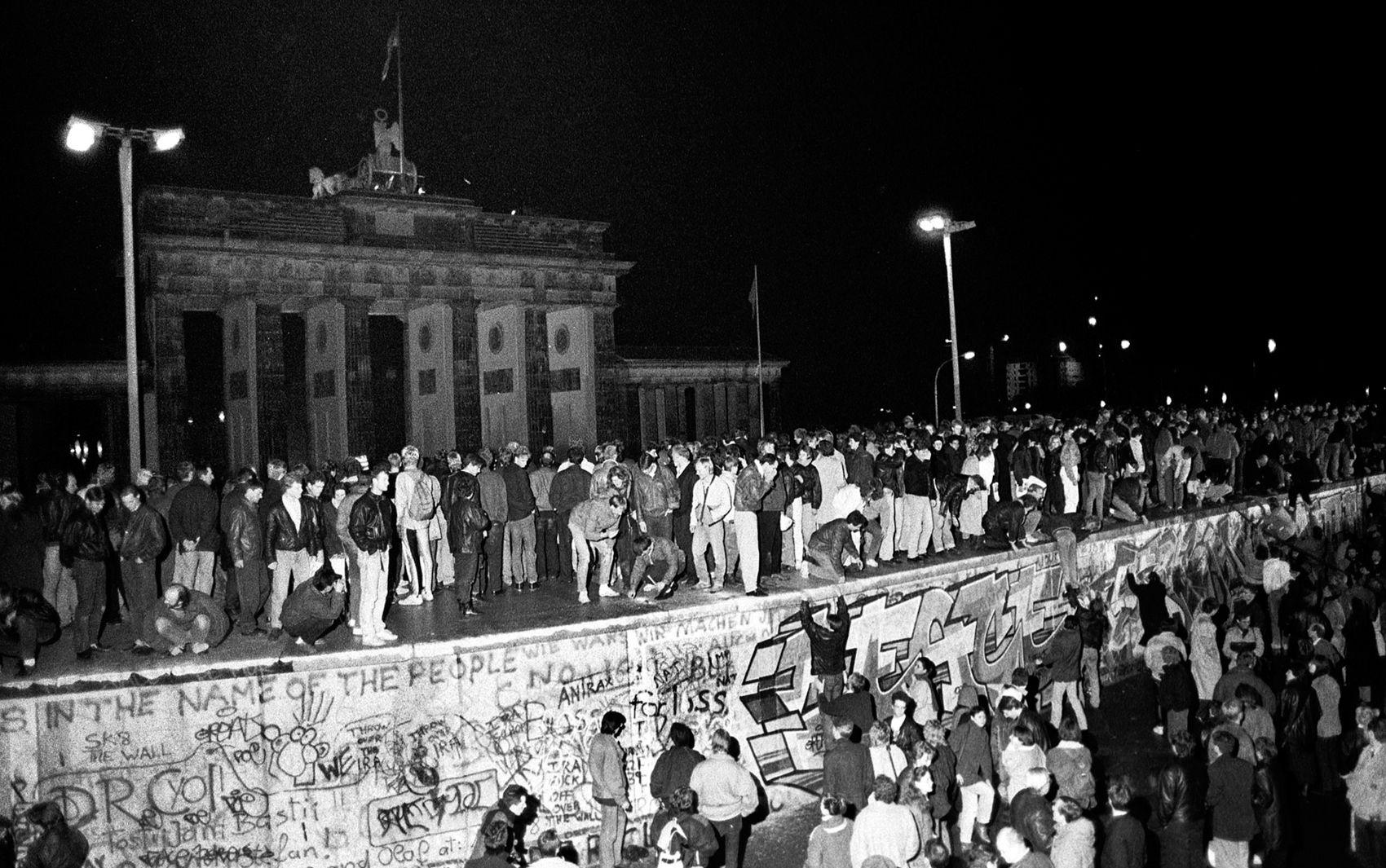 Foto de arquivo de 9 de novembro de 1989 mostra cidadãos da Alemanha oriental e ocidental comemorando ao subir no muro de Berlim no Portão de Brandemburgo, após a abertura da fronteira da Alemanha Oriental ser anunciada em Berlim