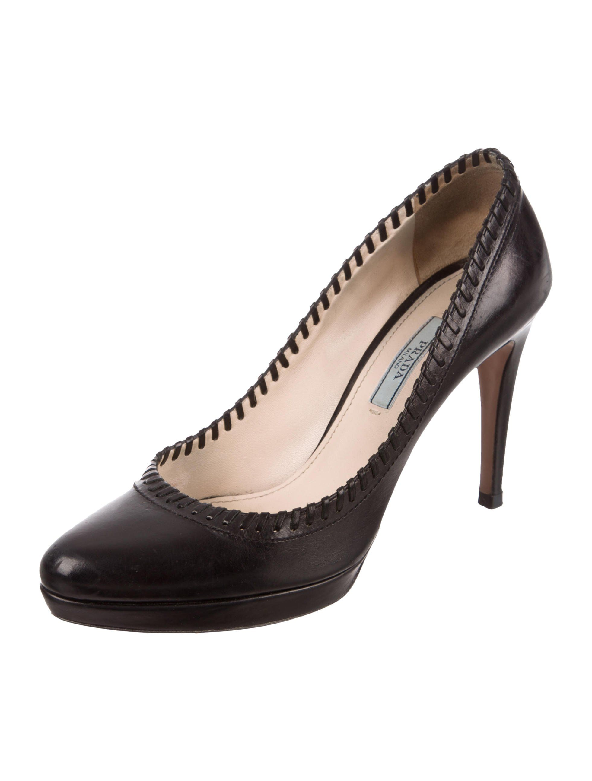03ec501ad6a Black leather Prada semi pointed-toe platform pumps with tonal whipstitched  trim at top lines and covered heels. Includes dust bag.