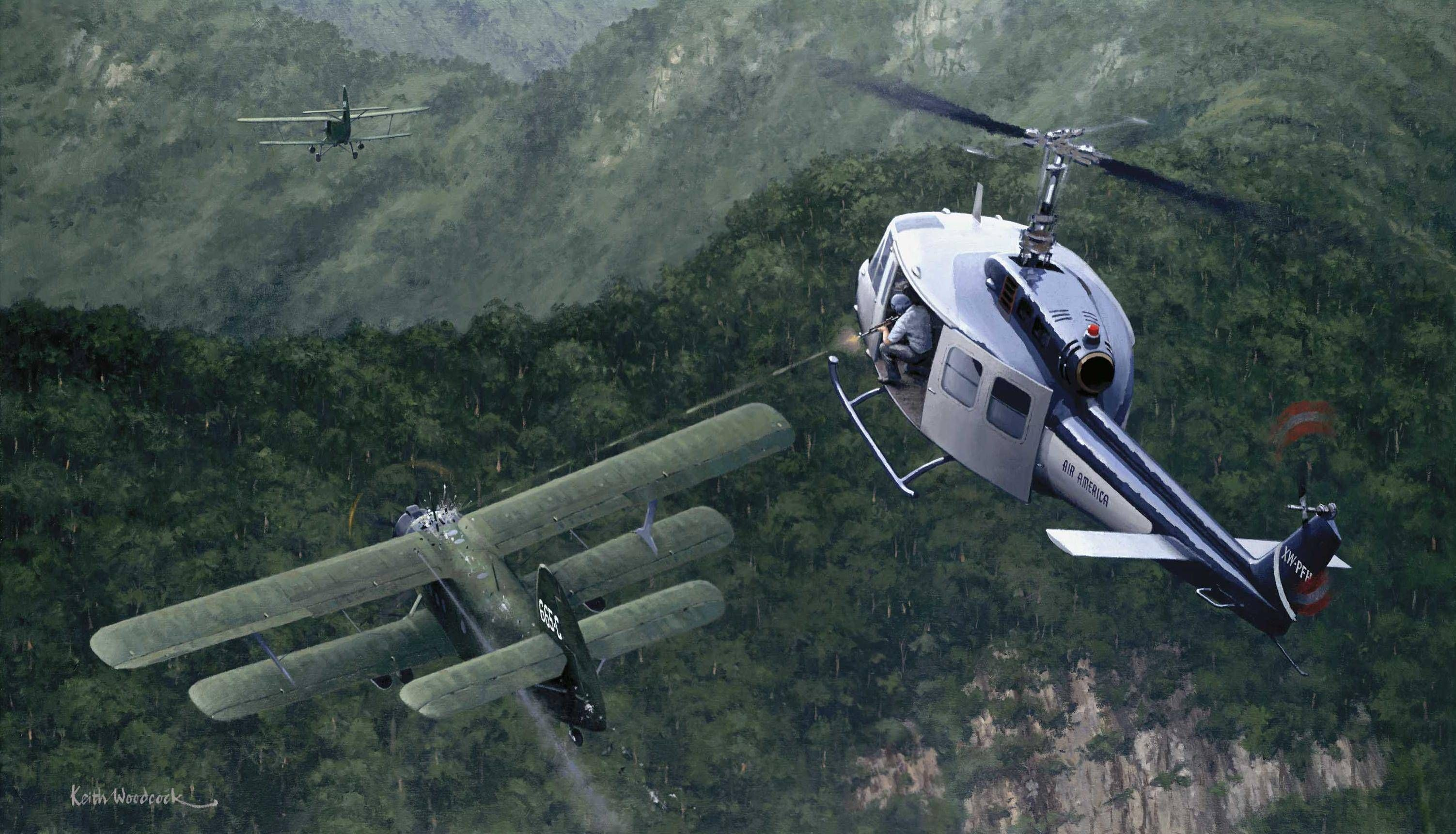 An Air America Bell helicopter shooting down an attacking North Vietnamese Air Force An-2 Colt ...