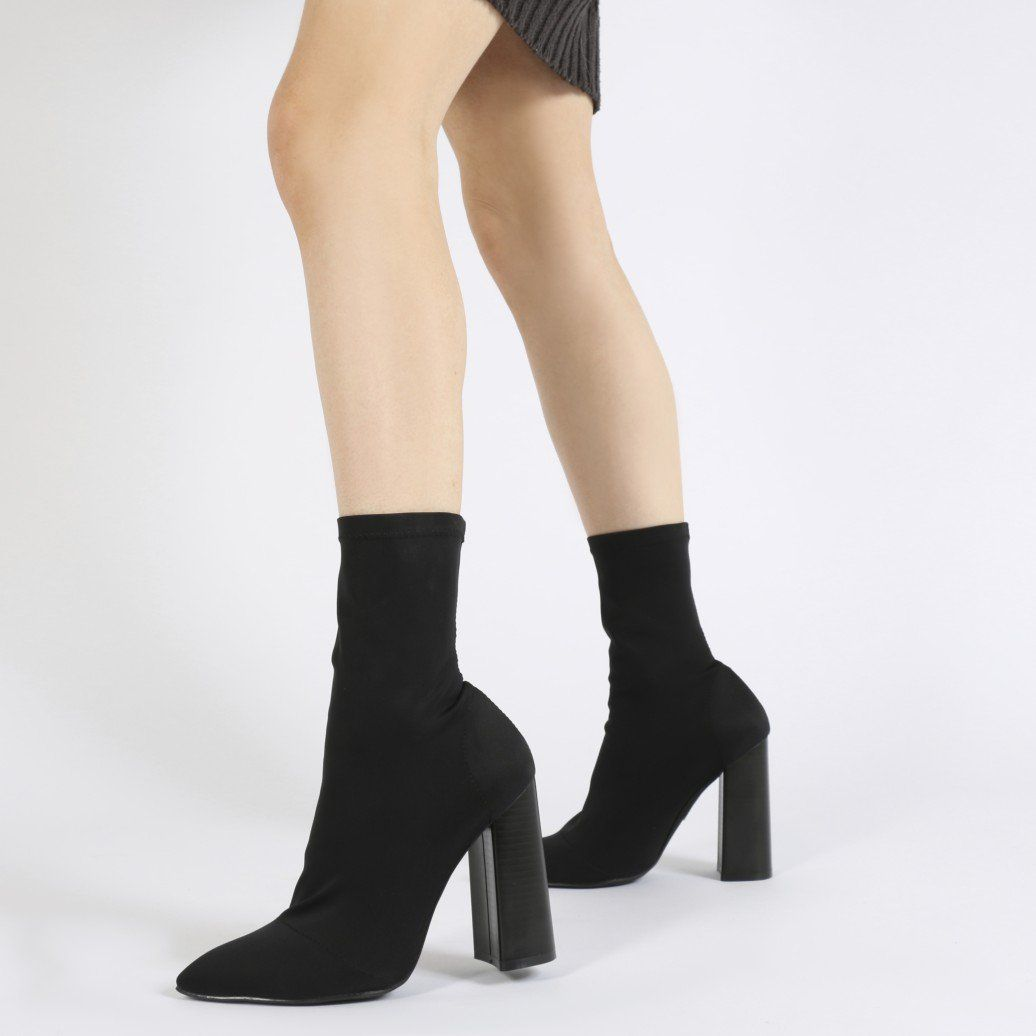 Ultimate luxe looks in this tight sock fit stretch ankle booties. Featuring  a pointed toe and flared wooden effect stacked block heel.